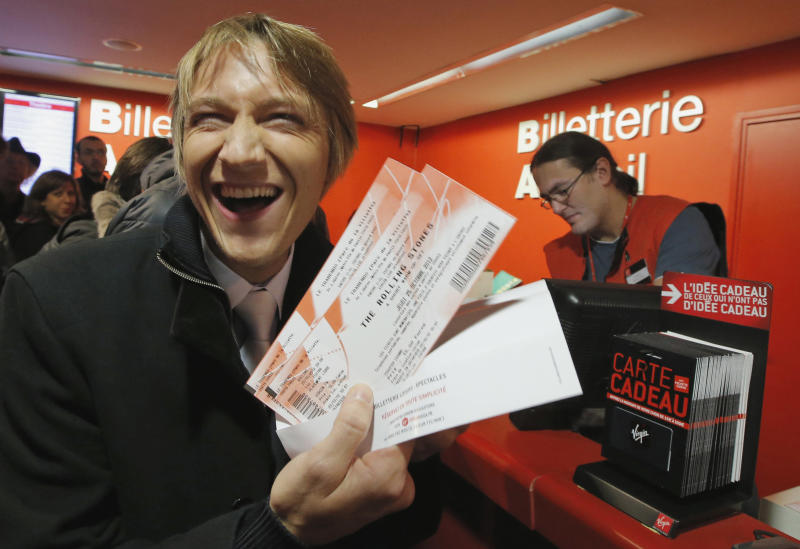 "Michael Evanno, 31, shows the tickets he bought for the Rolling Stones concert at Virgin Megastore in Paris, Thursday Oct. 25, 2012. The Rolling Stones announced a surprise ""warm-up gig"" in Paris, and within an hour the Champs Elysees was swarming with fans hoping to get satisfaction with one of the 350 tickets for the Thursday night show. (AP Photo/Francois Mori)"