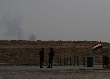 Smoke rises as Syrian army soldiers stand near a checkpoint in Deir al-Zor