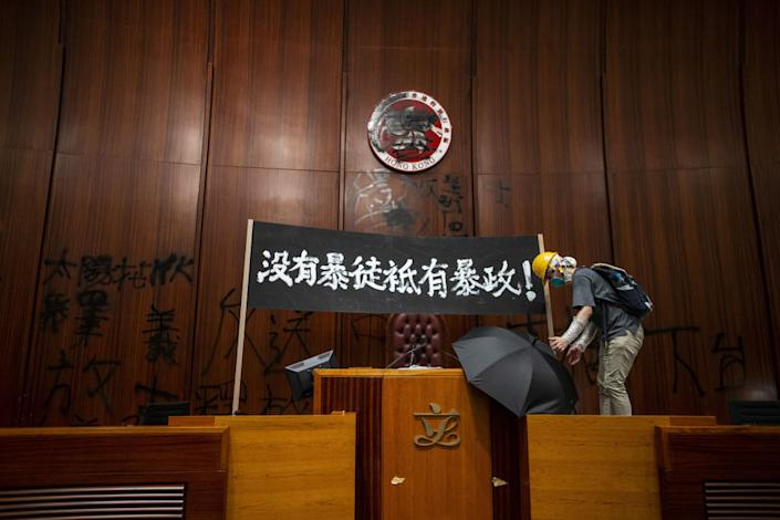 """A demonstrator places an umbrella next to a banner reading 'There are no rioters, only tyranny' in Chinese, displayed inside the chamber of the Legislative Council in Hong Kong, China, on Monday, July 1, 2019.span class=""""copyright""""Justin Chin/Bloomberg via Getty Images/span"""