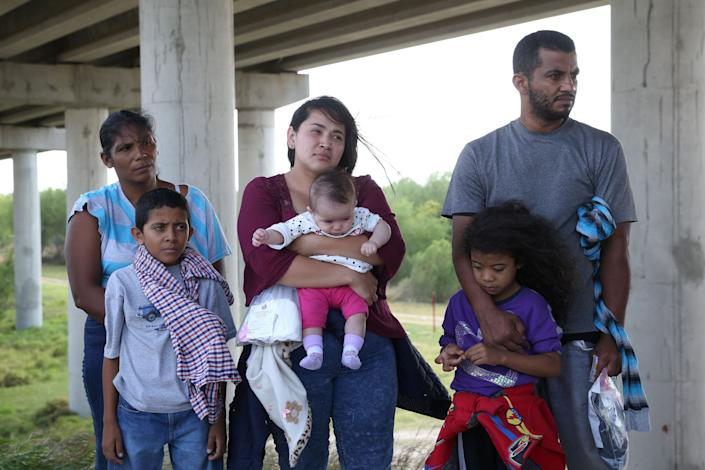 Undocumented immigrants who turned themselves in after crossing the border from Mexico into the U.S. await processing near McAllen, Texas,on April 2, 2018.