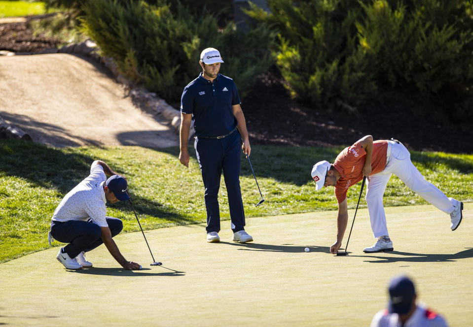 Jason Day, from left, Jon Rahm, and Andrew Landry prepare for putt shots at the 13th green during the third round of the CJ Cup golf tournament at Shadow Creek Golf Course, Saturday, Oct. 17, 2020, in North Las Vegas. (Chase Stevens/Las Vegas Review-Journal via AP)