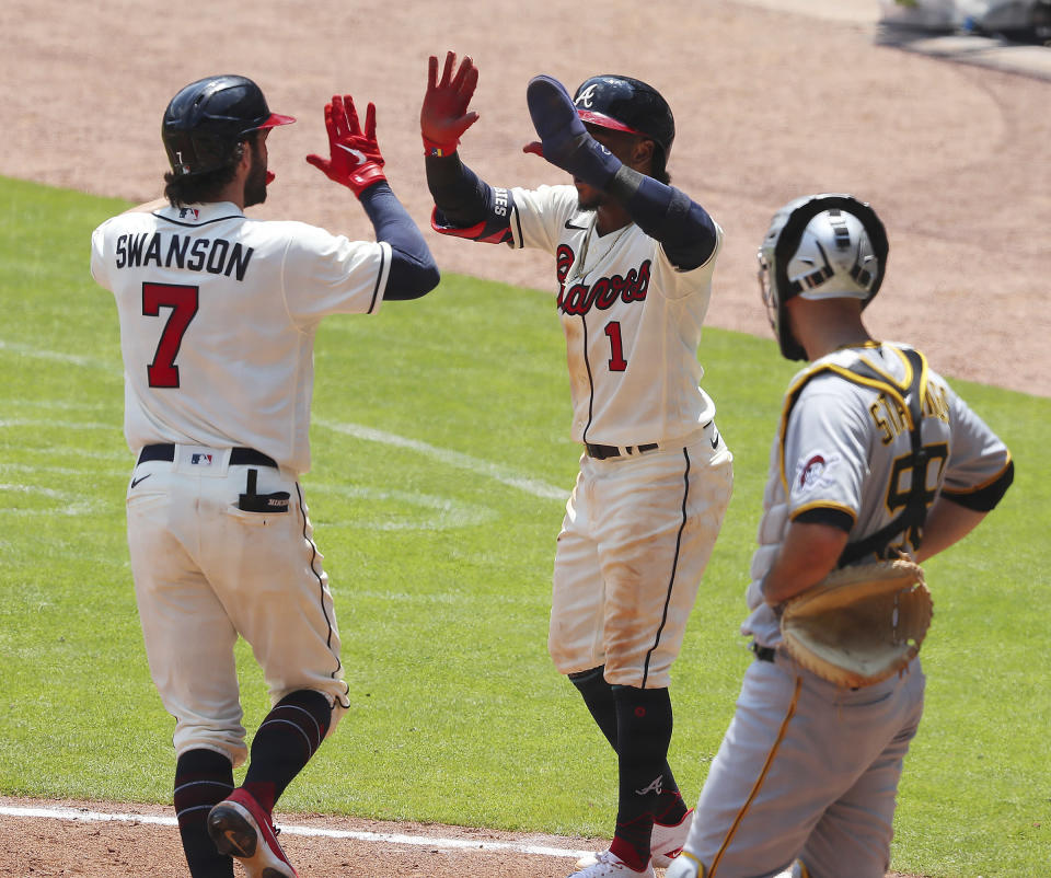 Atlanta Braves batter Dansby Swanson, left, gets a double high-five from teammate Ozzie Albies after hitting a two-RBI home run against the Pittsburgh Pirates during a baseball game Sunday, May 23, 2021, in Atlanta. (Curtis Compton/Atlanta Journal-Constitution via AP)