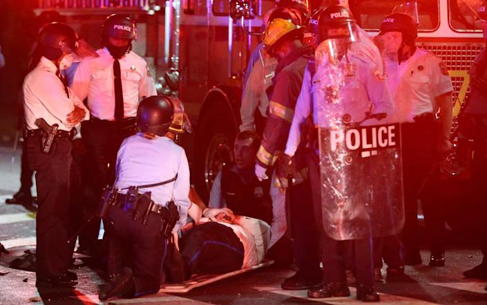 A police officer lies on the ground before being loaded into an ambulance on 52nd Street in West Philadelphia - Tim Tai /The Philadelphia Inquirer