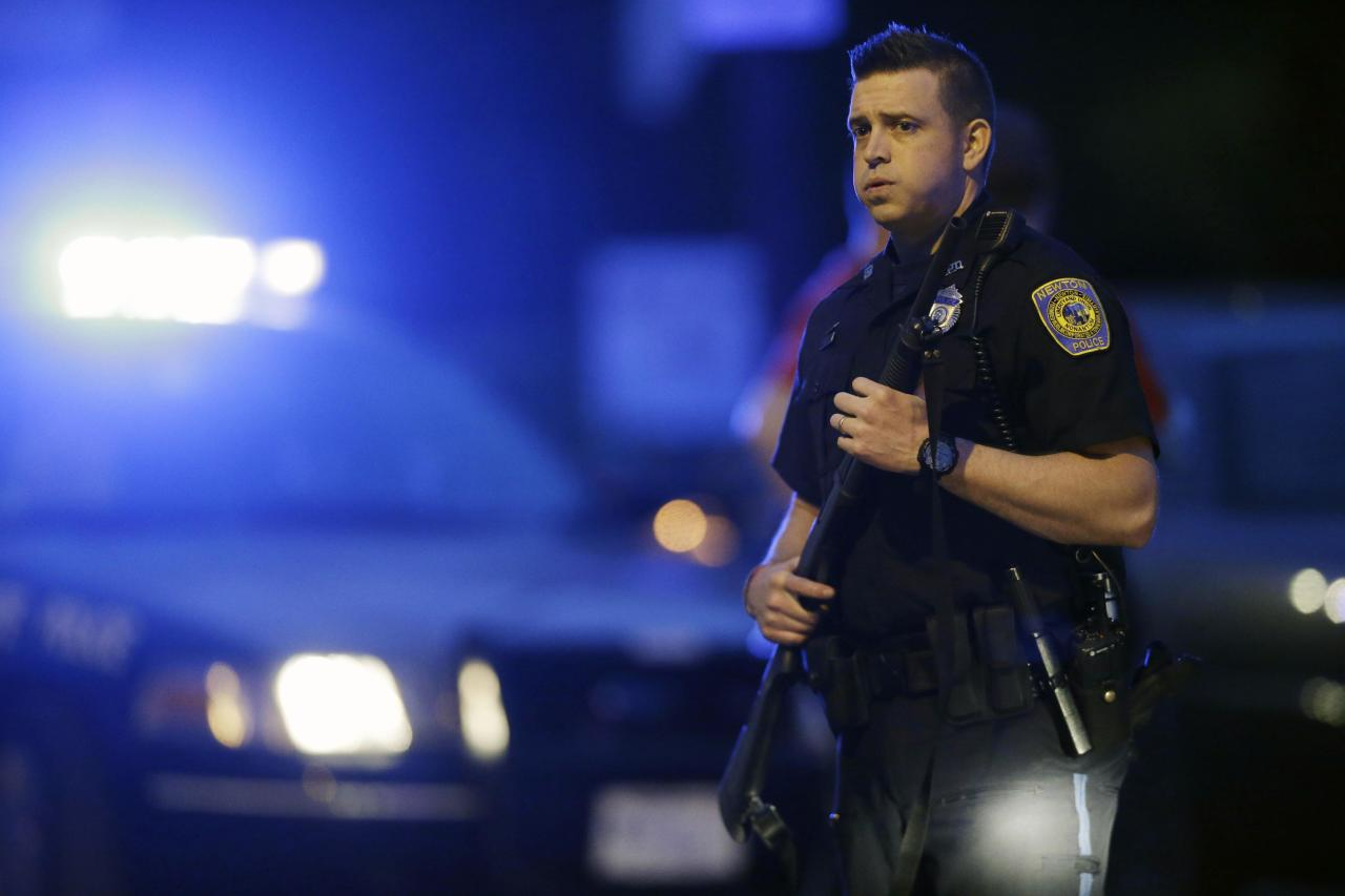 A police officer stands guard at the scene as the search for suspect in the Boston Marathon bombings continues , Friday, April 19, 2013, in Watertown, Mass. Gunfire erupted Friday night amid the manhunt for the surviving suspect in the Boston Marathon bombing, and police in armored vehicles and tactical gear rushed into the Watertown neighborhood in a possible break in the case. (AP Photo/Matt Rourke)