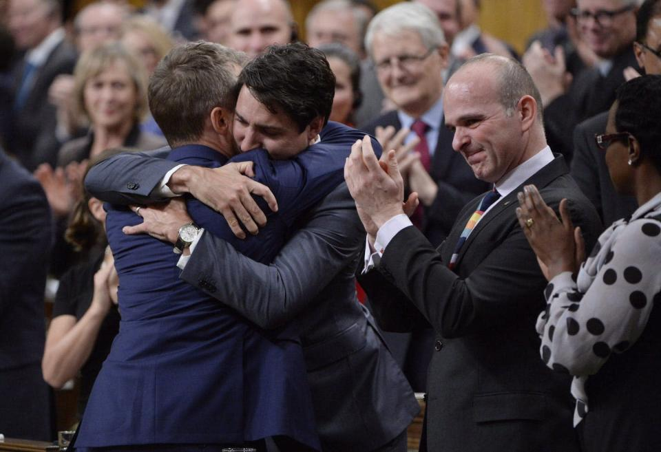 Justin Trudeau hugs a man while others clap in the background