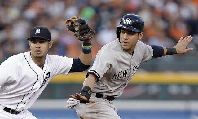 New York Yankees' Jacoby Ellsbury, right, signals safe after stealing second base as Detroit Tigers shortstop Eugenio Suarez holds the ball in the third inning of a baseball game in Detroit, Wednesday, Aug. 27, 2014. (AP Photo/Paul Sancya)