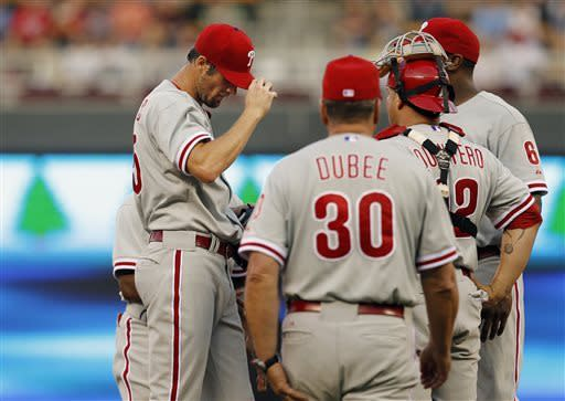 Philadelphia Phillies pitching coach Rich Dubee (30) approaches the mound to talk to starting pitcher Cole Hamels, left, during the fourth inning of a baseball game against the Minnesota Twins, Tuesday, June 11, 2013, in Minneapolis. (AP Photo/Genevieve Ross)