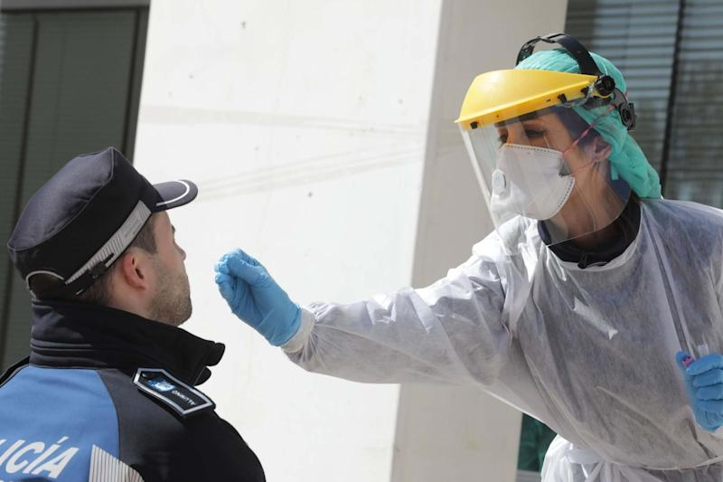 A health worker handling a swab to test a police officer in Madrid (Madrid City Hall/AFP via Getty I)