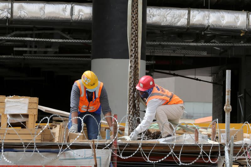 Foreign workers wearing protective face masks and gloves work at a construction site, following the outbreak of the coronavirus disease (COVID-19), in Riyadh