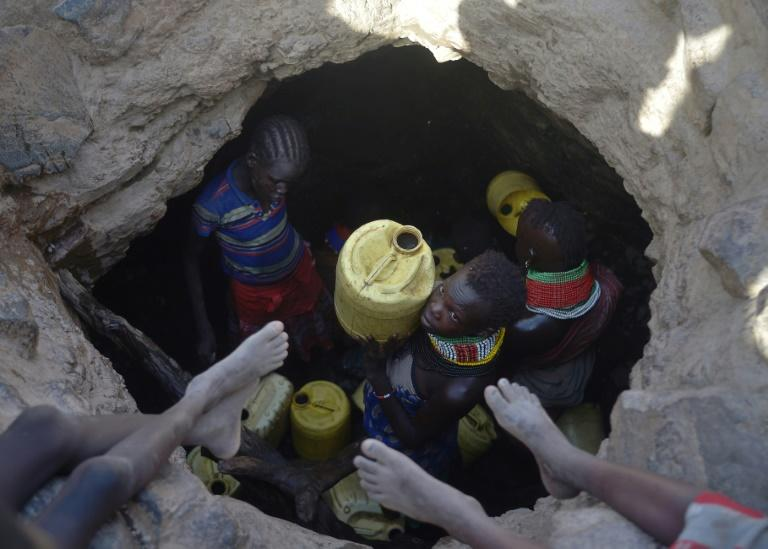 A young girl passes up a jerrycan filled with murky water from underground rocks in northern Kenya's Turkana county. A crippling drought ravaged the livestock population last year