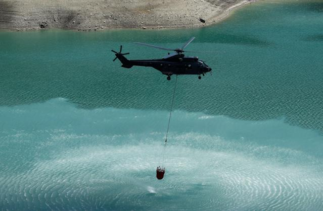 <p>A Swiss Air Force Super Puma helicopter loads water for cows in the Lac d'Hongrin due to an ongoing drought near Chateau d'Oex, Switzerland, Aug. 7, 2018. (Photo: Denis Balibouse/Reuters) </p>