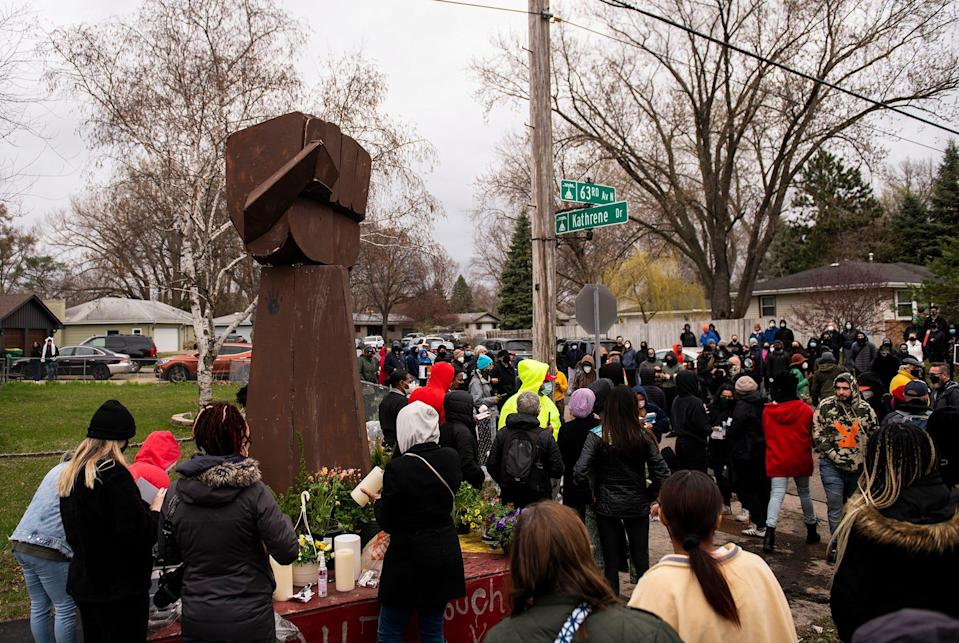 People gather around a sculpture of a raised fist during a vigil for Daunte Wright on April 12, 2021 in Brooklyn Center, Minnesota. Wright was shot and killed yesterday by Brooklyn Center police during a traffic stop. The fist sculpture first appeared over the summer at the memorial for George Floyd, the artist Jordan Powell-Karis brought it to the site where Wright was killed today.