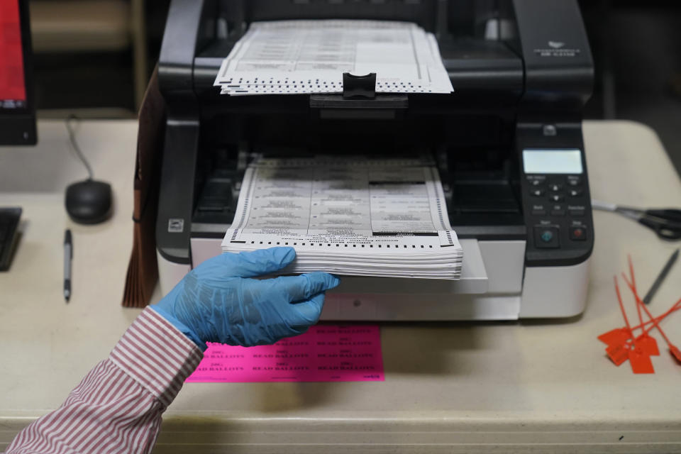 A county worker loads mail-in ballots into a scanner that records the votes at a tabulating area at the Clark County Election Department, Thursday, Oct. 29, 2020, in Las Vegas. (AP Photo/John Locher)