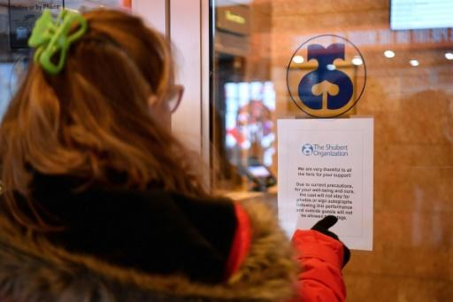 A woman reads a sign at Shubert Theater in New York's Broadway theater district announcing closures over coronavirus