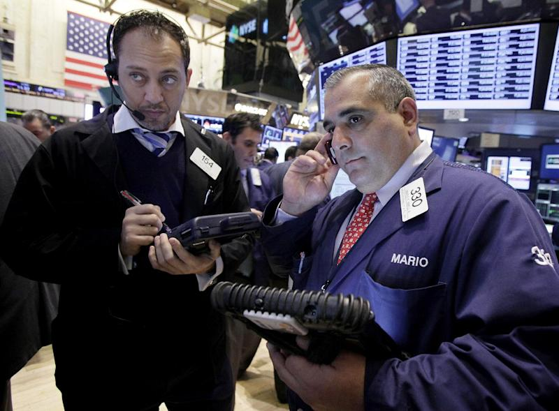 Traders Fady Tanios, left, and Mario Innella work on the floor of the New York Stock Exchange Tuesday, Dec. 11, 2012. Stocks opened higher Tuesday ahead of a meeting of the Federal Reserve and possible additional steps to bolster the U.S. economy. (AP Photo/Richard Drew)