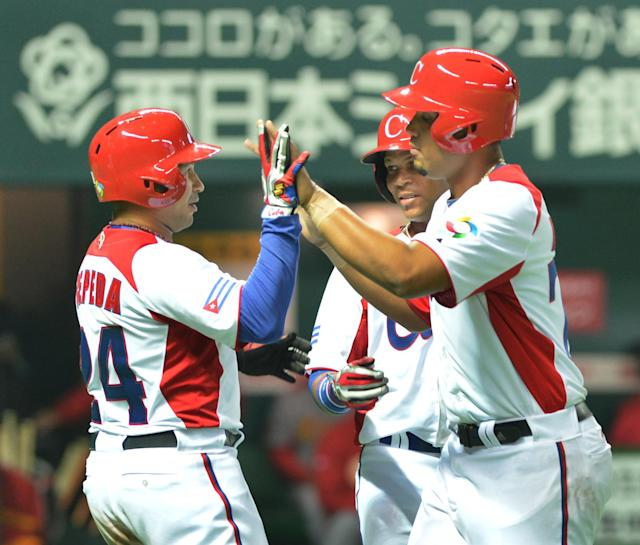 Cuba's Jose Abreu (R) is congratulated by teammates after his grand slam against China during the fifth inning of their first-round Pool A game in the World Baseball Classic tournament in Fukuoka on March 4, 2013. AFP PHOTO / KAZUHIRO NOGIKAZUHIRO NOGI/AFP/Getty Images
