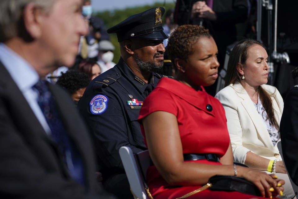 U.S. Capitol Police Sgt. Harry Dunn, second from left, listens during an event before the signing of a bill in the Rose Garden of the White House, in Washington, Thursday, Aug. 5, 2021, that awards Congressional gold medals to law enforcement officers that protected members of Congress at the Capitol during the Jan. 6 riot. (AP Photo/Evan Vucci)