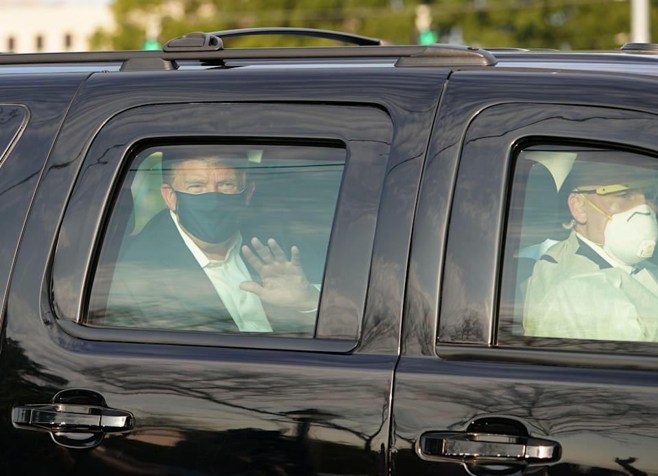 US president Trump waves from the back of a car in a motorcade outside of Walter Reed Medical Centre in Bethesda, Maryland on 4 October 2020 ((AFP via Getty Images))