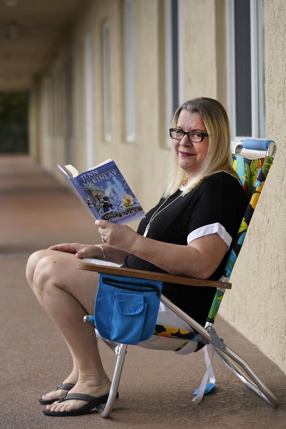 Kelly Vaiman poses for a photo along a walkway to her home where she likes to sit and read, Friday, Feb. 19, 2021, in Boynton Beach, Fla. Vaiman is an avid cozy mystery reader. (AP Photo/Wilfredo Lee)