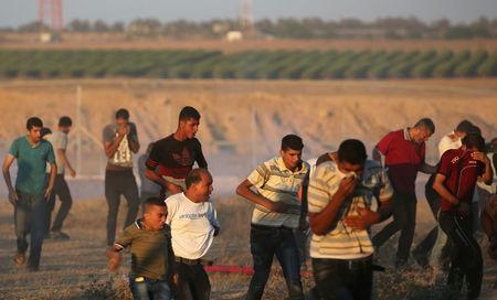 Palestinian demonstrators run as tear gas was fired by Israeli troops during a protest at the Israel-Gaza border, in the southern Gaza Strip July 27, 2018. REUTERS/Ibraheem Abu Mustafa