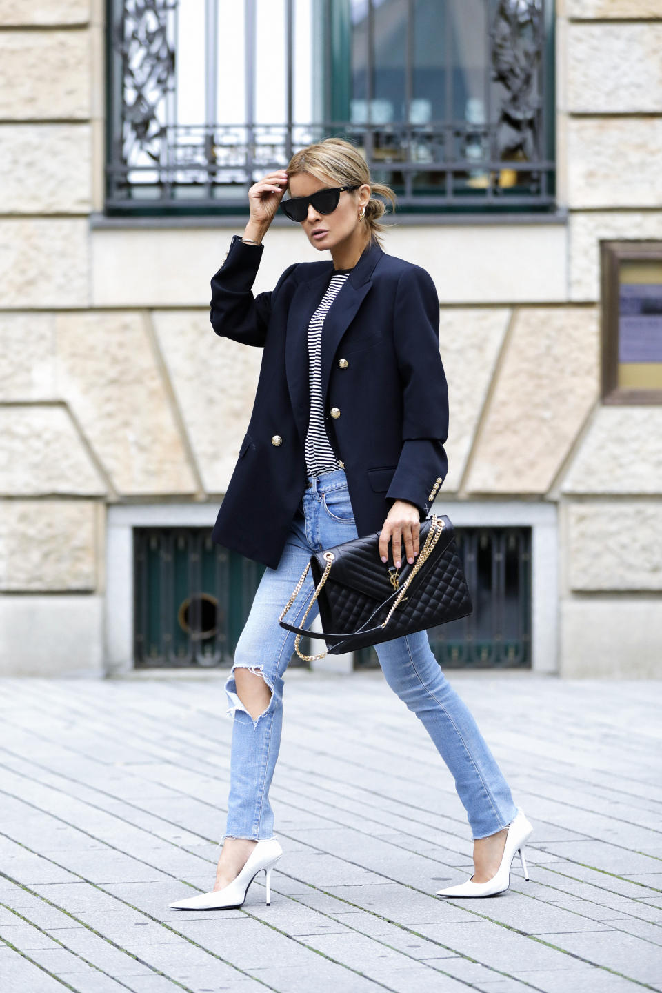 DUSSELDORF, GERMANY - SEPTEMBER 08: Influencer Gitta Banko wearing a blue and white striped t-shirt by Celine and a dark blue blazer by Celine with gold buttons, light blue skinny denim jeans by Balenciaga, white pumps by Balenciaga, a black bag by Saint Laurent, sunglasses by Bottega Veneta, gold earrings by Balenciaga and silver and gold bracelets by Celine during a street style shooting on September 8, 2020 at Breuninger in Dusseldorf, Germany. (Photo by Streetstyleshooters/Getty Images)