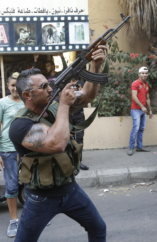 A Lebanese Shiite gunman fires his AK-47 during the funeral procession of Hamad al-Mekdad, 42, who was killed on Thursday by a car bomb in a predominantly Shiite area and stronghold of the Lebanese militant group Hezbollah, in a southern suburb of Beirut, Lebanon, Friday, Aug. 16, 2013. Lebanese forensic experts collected evidence Friday at the scene of a massive explosion in a southern suburb of Beirut that killed dozens of people and wounded hundreds, the deadliest blast in the area in nearly three decades. (AP Photo/Hussein Malla)
