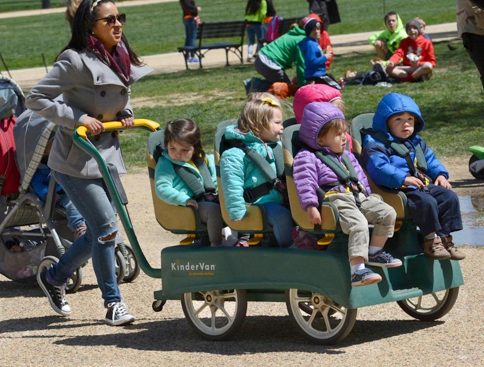 """WASHINGTON, D.C. - APRIL 20, 2018: A daycare center employee pushes a KinderVan filled with preschool children on an outing along the National Mall in Washington, D.C.<span class=""""copyright"""">Getty Images—Robert Alexander</span>"""