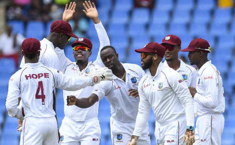 Kemar Roach (C), Shimron Hetmyer (3L), John Campbell (3R), Kraigg Brathwaite (2R) and Sharmarh Brooks (R) of West Indies celebrate the dismissal of Cheteshwar Pujara of India during day 1 of the 1st Test between West Indies and India at Vivian Richards Cricket Stadium in North Sound, Antigua and Barbuda, on August 22, 2019. (Photo by Randy Brooks / AFP)