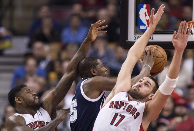Toronto Raptors forward Amir Johnson, left, and Jonas Valanciunas, right, defend against Oklahoma Thunder forward Kevin Durant, center, during the first half of an NBA basketball game in Toronto on Friday, March 21, 2014. (AP Photo/The Canadian Press, Nathan Denette)