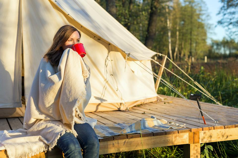Young woman wraps blanket over herself while sitting and drinking coffee near canvas tent in the morning in the woods