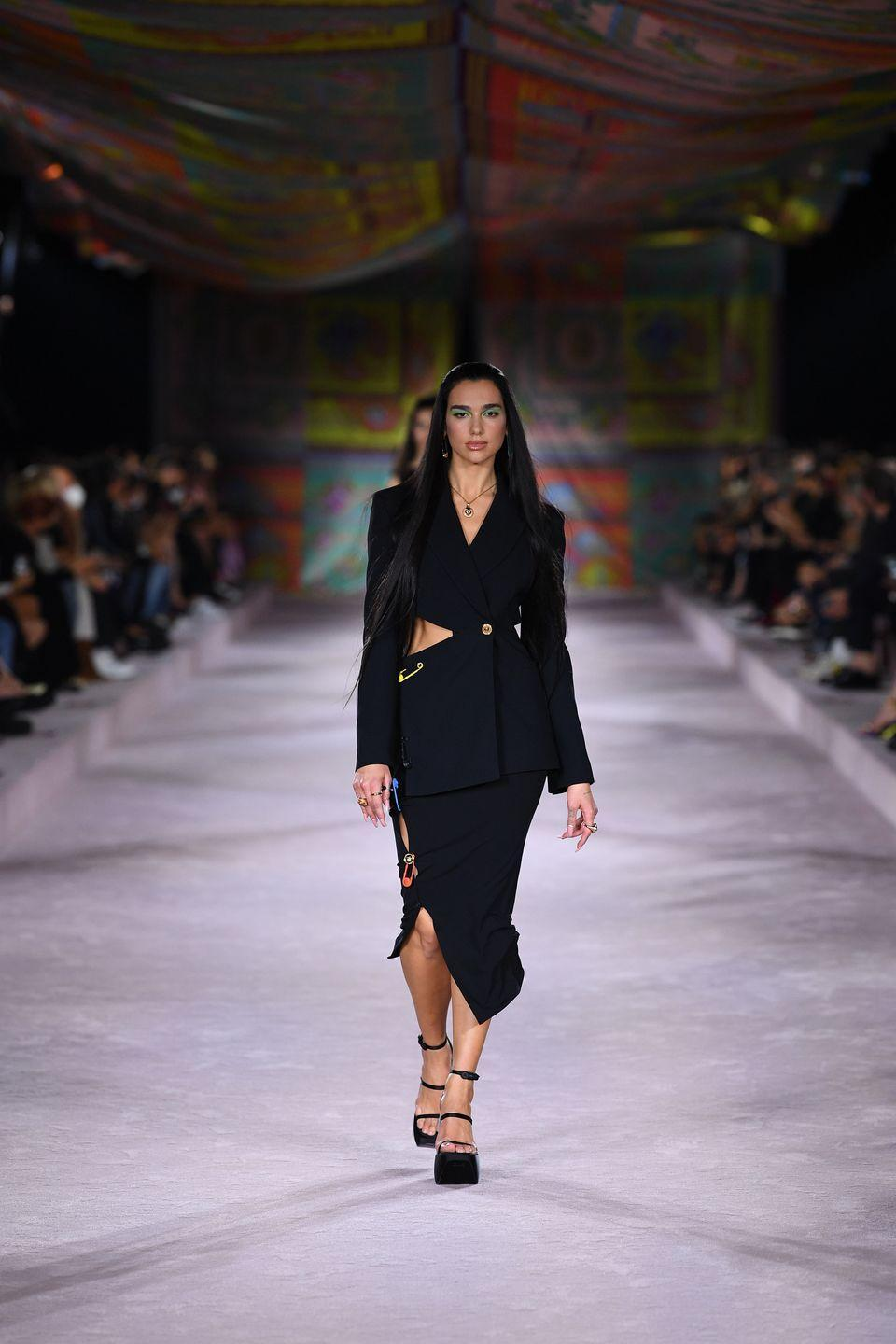"""<p>Making her catwalk debut, British-Albanian star Dua Lipa stormed Versace's SS22 runway at Milan Fashion Week.</p><p>Lipa took to <a href=""""https://www.instagram.com/p/CUOII1vMzHy/"""" rel=""""nofollow noopener"""" target=""""_blank"""" data-ylk=""""slk:Instagram"""" class=""""link rapid-noclick-resp"""">Instagram</a> to share her delight, writing: 'such an honour to open and close the [Versace] show tonight in Milan.'</p><p>'[Donatella Versace] you know i'll be your Versace girl forever [sic]', the 26 year-old wrote. </p>"""