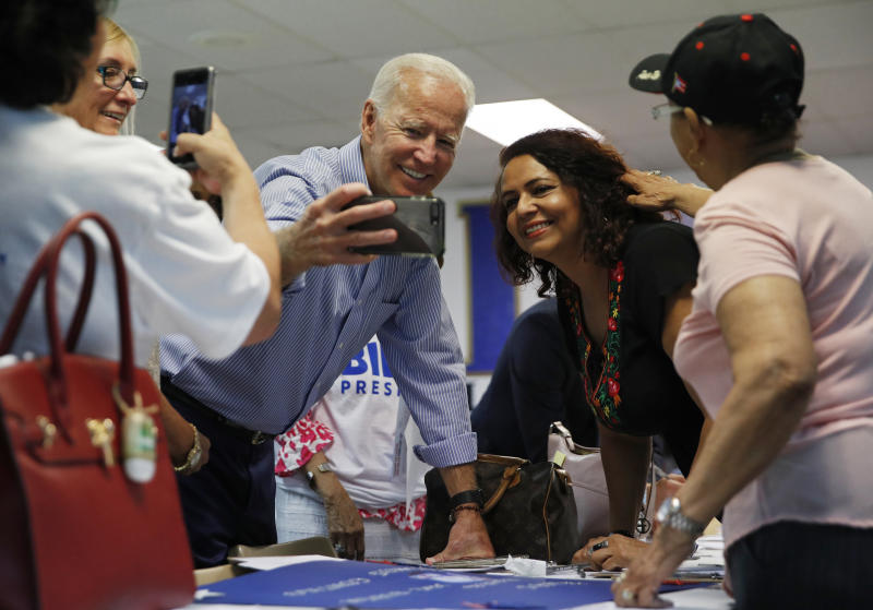 FILE - In this July 20, 2019, file photo, former Vice President and Democratic presidential candidate Joe Biden takes a selfie with a supporter during a campaign event at an electrical workers union hall in Las Vegas. More than traditional markers of electability like name recognition, fundraising ability or charisma, the path to the Democratic nomination runs through black voters.  (AP Photo/John Locher, File)