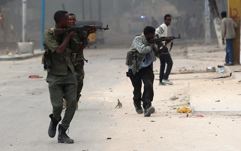 Somali government soldiers run to take their positions during gunfire after a suicide bomb attack outside Nasahablood hotel  - Feisal Omar/Reuters