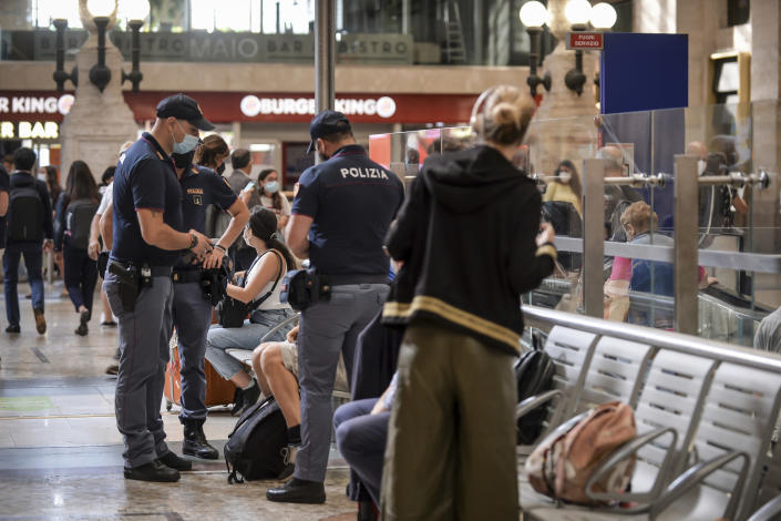 Italian police officers perform checks at Milan's Stazione Centrale train station, Italy, Wednesday, Sept. 1, 2021. The Italian government vowed to crack down on demonstrators threatening to block train tracks throughout the country on Wednesday as a rule requiring COVID-19 tests or vaccines takes effect for long-distance domestic public transport. (Claudio Furlan/LaPresse via AP)