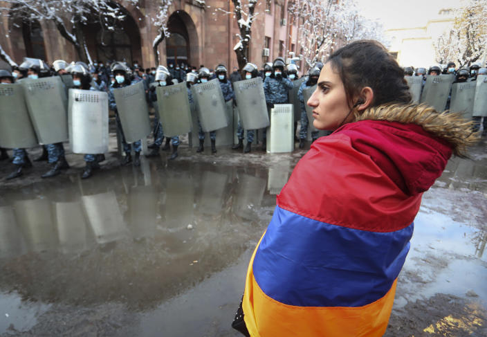 A woman wearing a state Armenian flag stands in front of a riot police line during a rally to pressure Armenian Prime Minister Nikol Pashinyan to resign over a peace deal with neighboring Azerbaijan on Republic Square in Yerevan, Armenia, Thursday, Dec. 24, 2020. Armenian opposition politicians and their supporters have been protesting for weeks, demanding the prime minister's resignation over his handling of the Nagorno-Karabakh conflict with Azerbaijan. (Vahram Baghdasaryan, Photolure via AP)