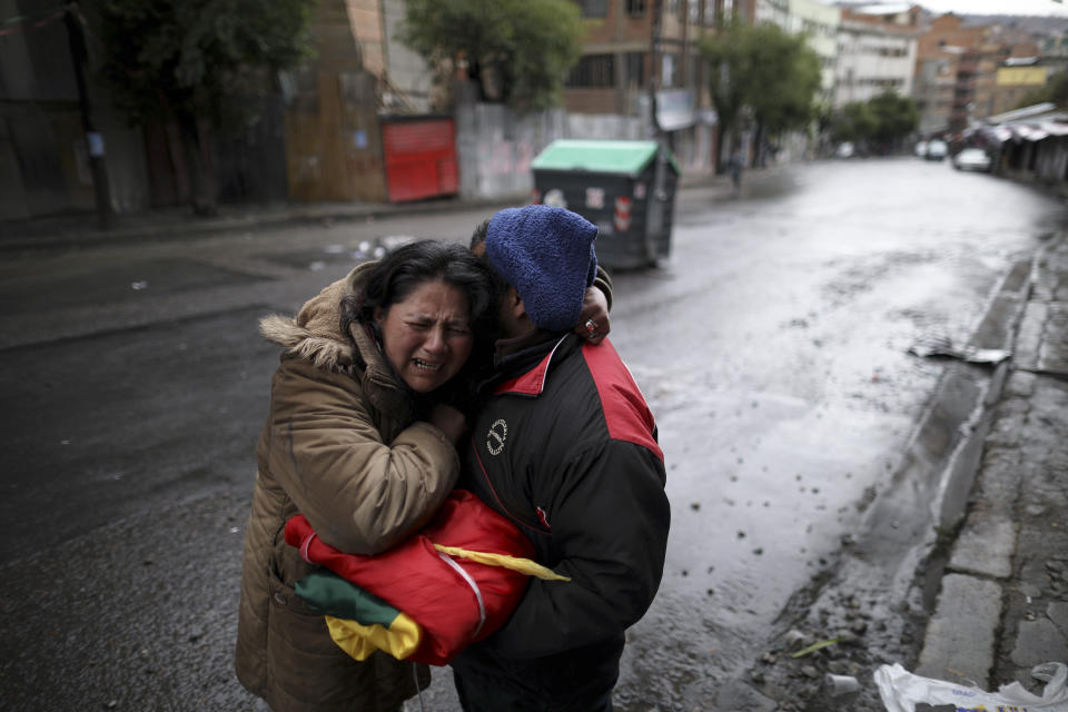 A couple, holding a Bolivian flag, embrace after spending the night celebrating the resignation of President Evo Morales in La Paz, Bolivia, Monday, Nov. 11, 2019. Morales resigned Sunday under mounting pressure from the military and the public after his re-election victory triggered weeks of fraud allegations and deadly protests.(AP Photo/Natacha Pisarenko)