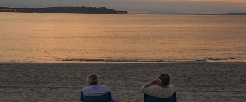 An older couple sit in portable fold-up chairs on the beach to watch the sunset, one talking on mobile phone, in Punta del Este, Uruguay