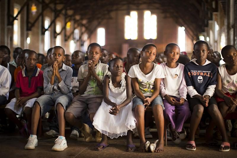 Rwandan children listen and pray during a Sunday morning service at the Saint-Famille Catholic church, the scene of many killings during the 1994 genocide, in the capital Kigali, Rwanda Sunday, April 6, 2014. Rwanda will commemorate on Monday the 20-year anniversary of the genocide when ethnic Hutu extremists killed neighbors, friends and family during a three-month rampage of violence aimed at ethnic Tutsis and some moderate Hutus, leaving a death toll that Rwanda puts at 1,000,050. (AP Photo/Ben Curtis)