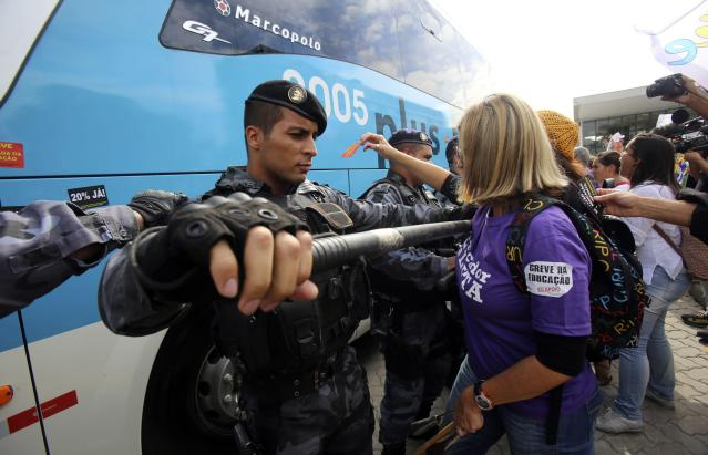 "A police officer tries to stop a protester from approaching a bus they think belongs to the Brazilian soccer team, during a demonstration outside a hotel where the Brazilian national soccer team are gathered, in Rio de Janeiro May 26, 2014. The Brazilian national soccer team will attend their first training session today. The sign reads: ""There will be no World Cup, there will be strike"". REUTERS/Ana Carolina Fernandez (BRAZIL - Tags: SPORT SOCCER)"