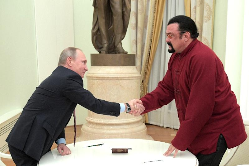 Vladimir Putin (left) shakes hands with Steven Seagal after presenting him with a Russian passport during a meeting at the Kremlin in Moscow, on November 25, 2016