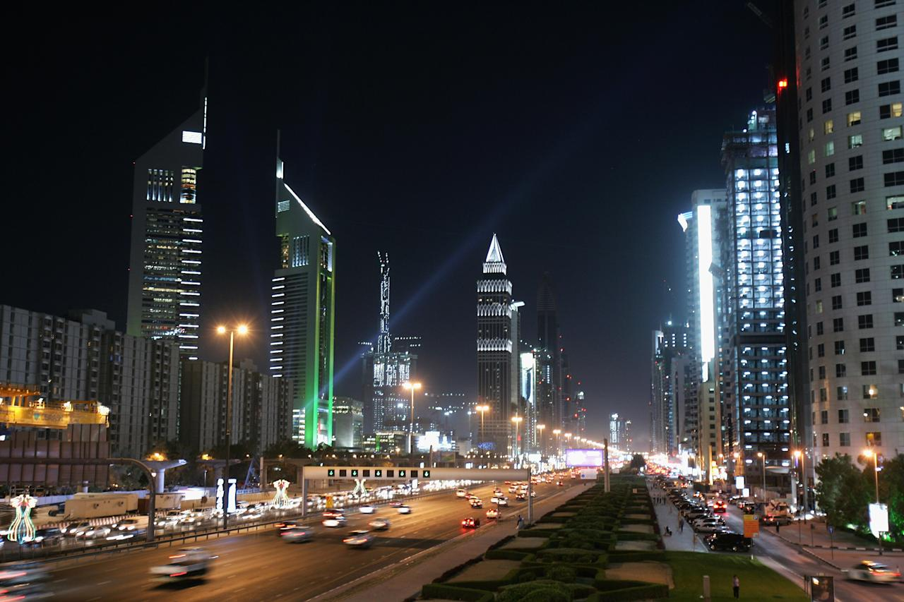 DUBAI, UNITED ARAB EMIRATES - DECEMBER 03: The iconic Emirates Towers dominate the skyline beside the wide boulevard of Sheikh Zayed Road on December 3, 2007 in Dubai, United Arab Emirates. The towers have been lit up this week to celebrate the 36th UAE National Day (Al-Eid Al Watani) on December 2nd. Over the last decade, Dubai has transformed into a futuristic city that now boasts the tallest building in the world (Al Burj). The exponential growth in the construction industry has led to problems such as excess traffic and congestion. A new metro line is due to be completed in 2008 in an attempt to alleviate the problem. (Photo by Chris Jackson/Getty Images)