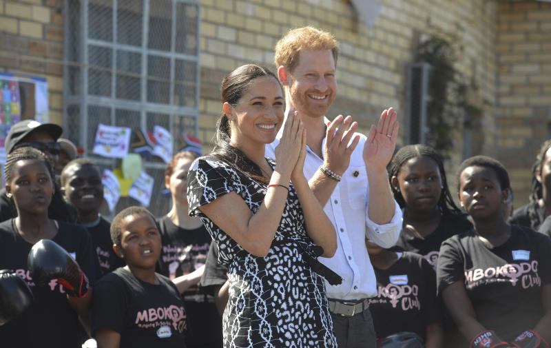 FILE - In this Monday, Sept, 23, 2019 file photo, Britain's Prince Harry and Meghan, Duchess of Sussex greet youths on a visit to the Nyanga Methodist Church in Cape Town, South Africa, which houses a project where children are taught about their rights, self-awareness and safety, and are provided self-defence classes and female empowerment training to young girls in the community. The final day of Prince Harry and his wife Meghan's 10-day visit to Africa with infant son Archie in tow has been overshadowed by a lawsuit she has filed against Britain's Mail on Sunday tabloid. (Courtney Africa/Pool via AP, File)