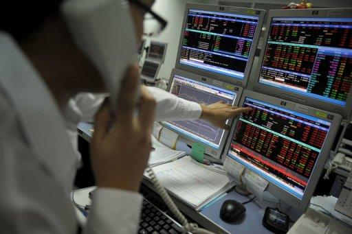 A Thai trader points at his computer screen as he speaks with a client on the phone at a private trading firm in Bangkok, 2011. Asian markets bounced back from recent loses following some much-needed positive news out of Europe and an IMF report forecasting global growth would be stronger than first thought