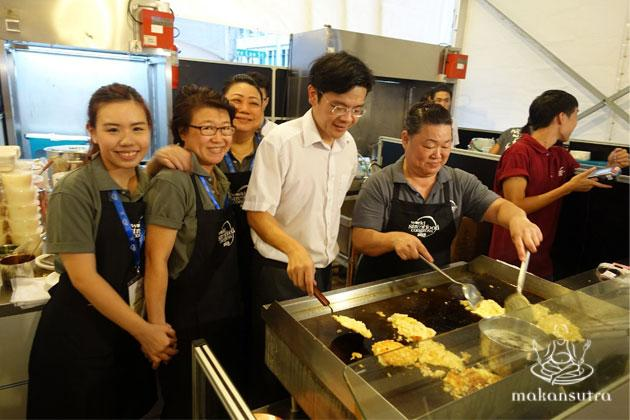 Minister Lawrence Wong having a go at fried carrot cake at the Singapore Pavillion.