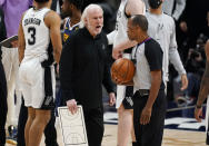 San Antonio Spurs head coach Gregg Popovich, front left, argues with referee Eric Lewis after the Spurs missed a shot to tie the contest late in the second half of an NBA basketball game against the Denver Nuggets, Friday, April 9, 2021, in Denver. (AP Photo/David Zalubowski)