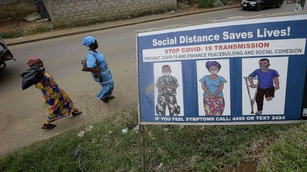 PHOTO: People walk past a billboard with coronavirus awareness campaign messages on a busy roadside in Monrovia, Liberia, Oct. 18, 2020. (Ahmed Jallanzo/EPA via Shutterstock)