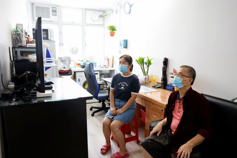 Lau Kai Fai, 70, sits inside his new home in a four-story building made from pre-fabricated parts with his wife at Shek Kip Mei, in Hong Kong