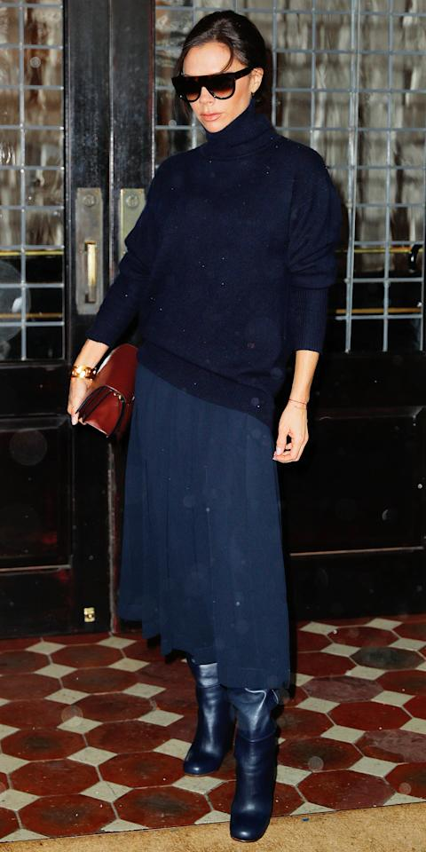 <p>Beckham made the case for monochrome in an all-navy outfit in New York, pairing a turtleneck sweater with a pleated midiskirt and matching leather boots. She added a pop of color with a red leather purse.</p>