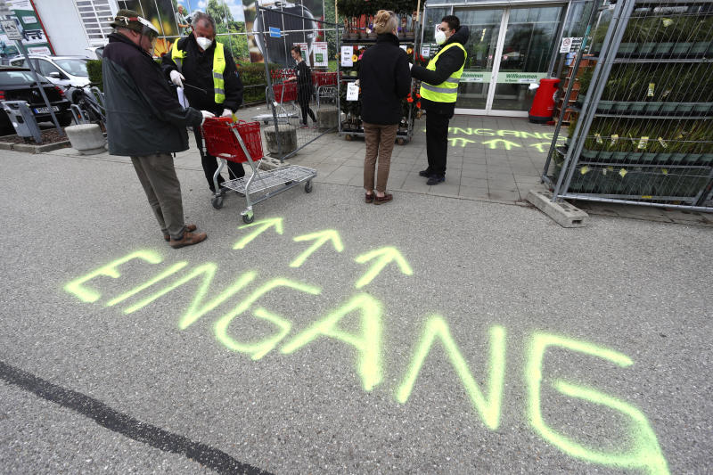 Security employee disinfect shopping carts at the entrance of a garden store in Munich, Germany, Monday, April 20, 2020. Europe's biggest economy, starts reopening some of its stores and factories after weeks of lockdown due to the new coronavirus outbreak. Word on the ground reads 'Entrance' (AP Photo/Matthias Schrader)