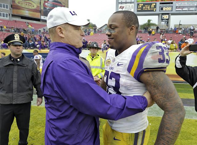 LSU head coach Les Miles, left, congratulates MVP Jeremy Hill (33) after LSU defeated Iowa 21-14 during the Outback Bowl NCAA college football game Wednesday, Jan. 1, 2014, in Tampa, Fla. (AP Photo/Chris O'Meara)